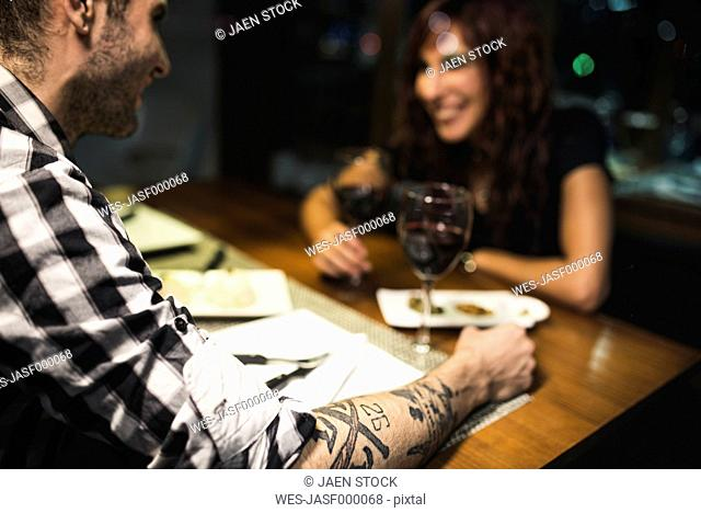 Tattooed arm of a young man having a rendezvous in a restaurant at night