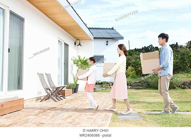Girl and her parents moving together to the new house representing rural living