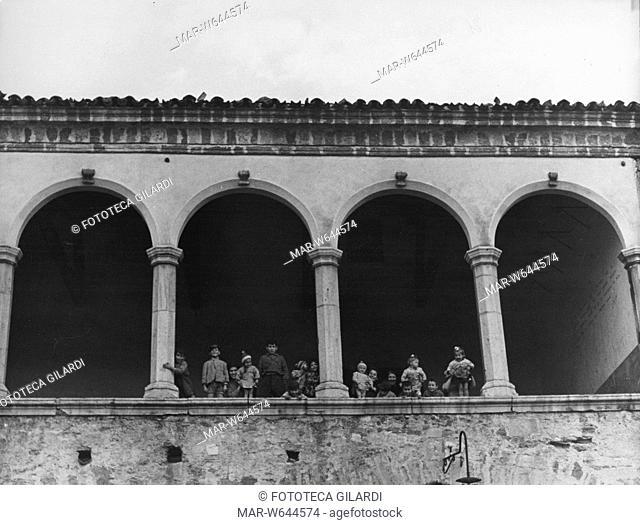 VENOSA bambini festosi in posa tra gli archi di un palazzo. Fotografia di Ando Gilardi  (1921-2012), parte di un ampio servizio realizzato per 'Lavoro'