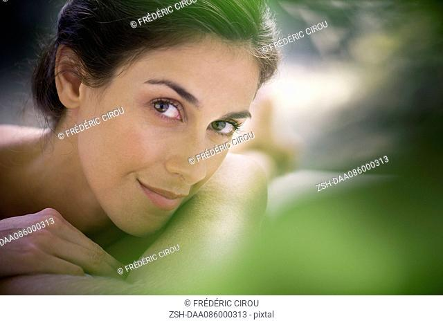 Woman lying on stomach, raising eyebrow, portrait