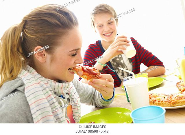 Young boy and girl eating pizza at dining room table