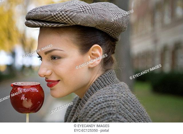 Portrait of young woman eating candy apple