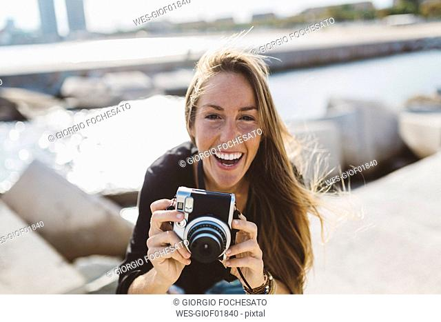 Portrait of happy young woman with old-fashioned camera at the seafront