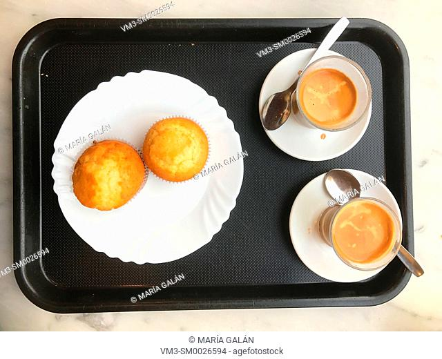 Two cups of coffee and two muffins on a tray. View from above