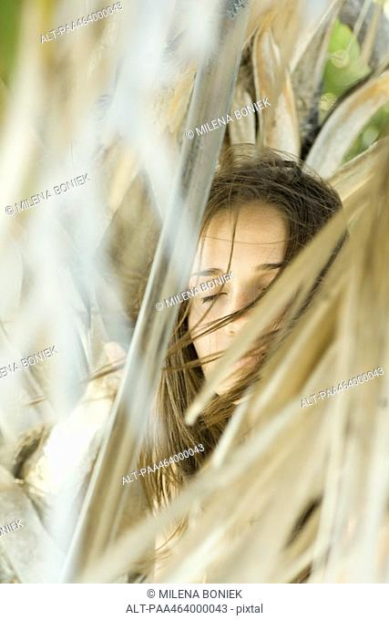 Woman closing eyes, hair blowing in wind, surrounded by dry foliage, selective focus
