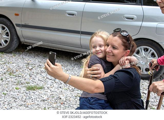 Inspired mom taking a selfie of her and daughter right in the middle of a parking lot age 6 and 34. Spala Central Poland
