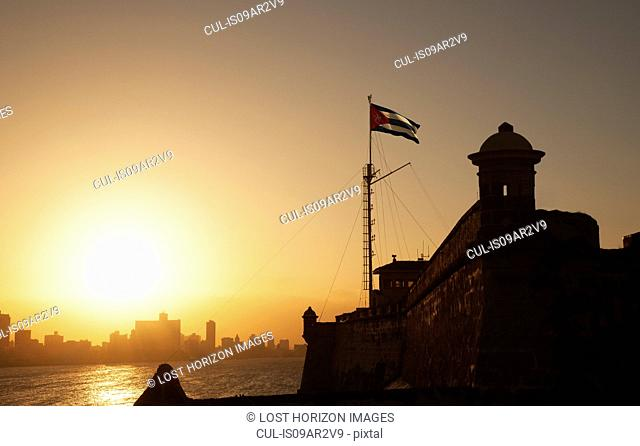 Cuban flag over El Morro Fortress at sunset, Havana, Cuba