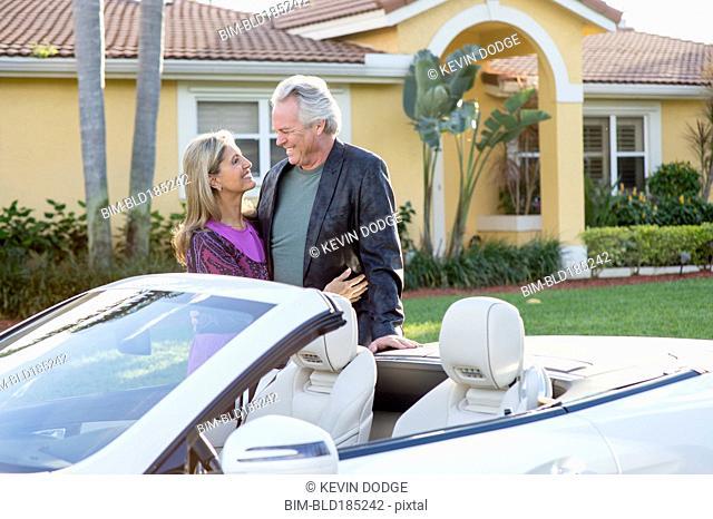 Caucasian couple smiling near convertible