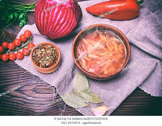 Traditional Ukrainian borsch in a round brown plate in the middle of vegetables and ingredients on a wooden table, top view