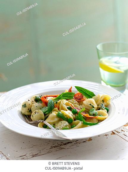 Bowl of orecchiette with peas and sage garnish