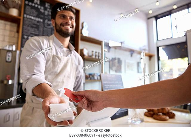Barista takes credit card payment at a coffee shop, close up