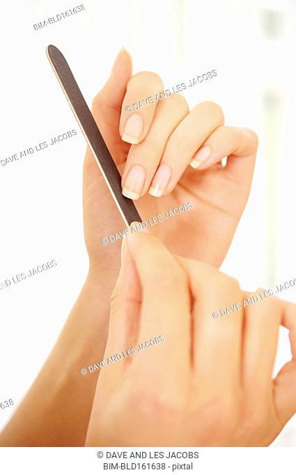 Caucasian woman filing fingernail