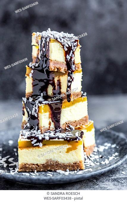 Cheesecake with mango orange cream, chocolate sauce and coconut flakes
