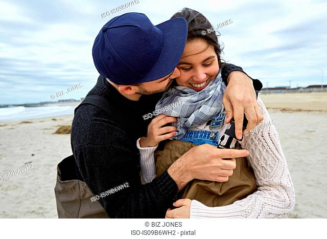 Romantic young sea fishing couple fastening waders on beach