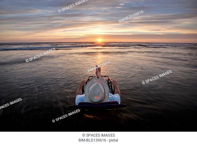 Caucasian man in deck chair overlooking sunset on beach