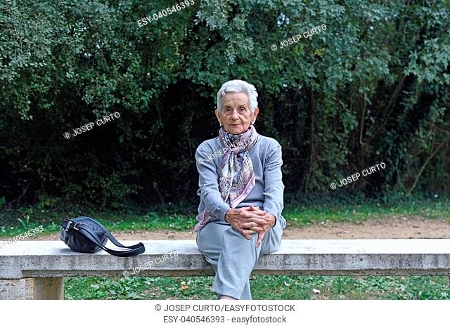 senior woman sitting alone on a bench in a park