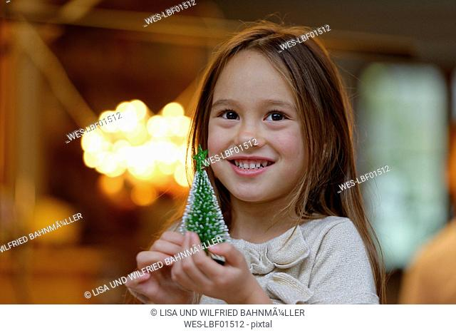 Portrait of smiling little girl with miniature Christmas tree