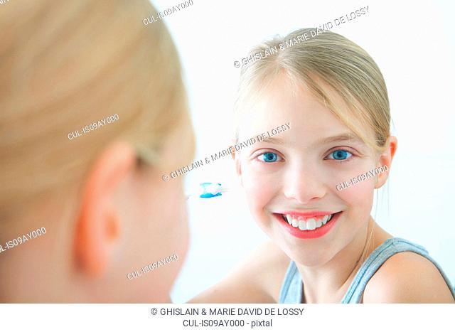Bathroom mirror portrait of girl holding toothbrush
