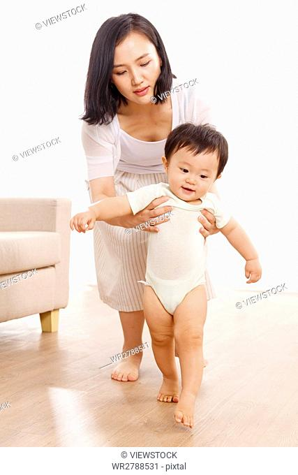 Mother helping baby boy learn to walk