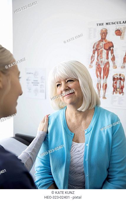 Caring female nurse talking to senior patient in clinic examination room