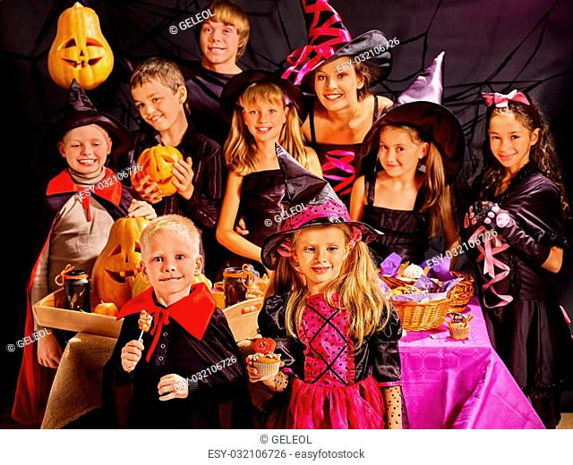 Children on Halloween party making carved pumpkin
