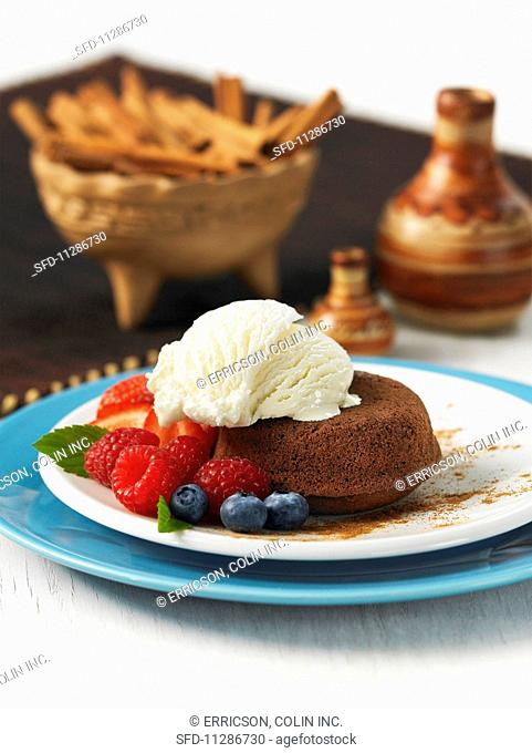 A mini chocolate cake with cinnamon, vanilla ice cream and fresh berries