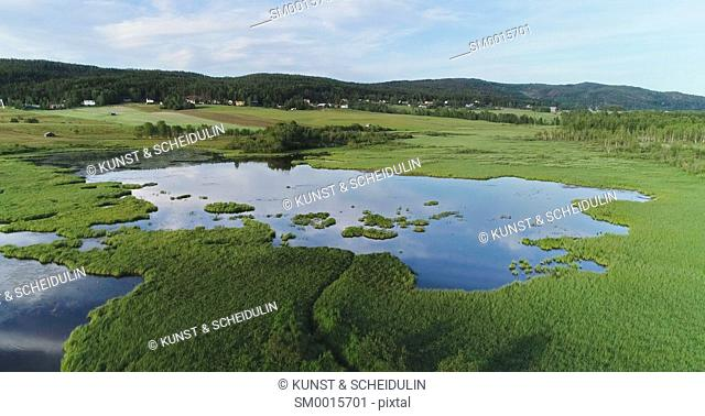 Aerial shot of a shallow lake surrounded by grassy marshland. Västernorrland, Sweden, Europe