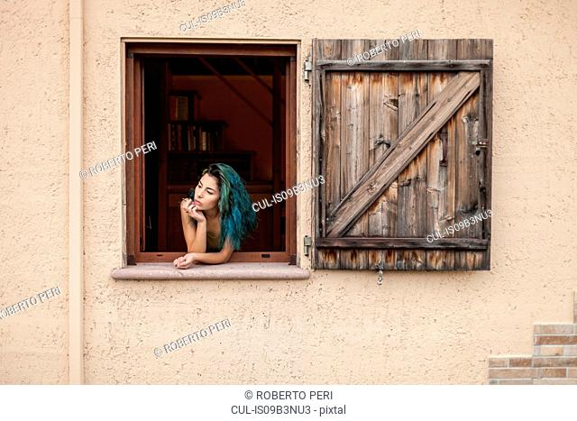 Young woman with blue hair, looking out of open window
