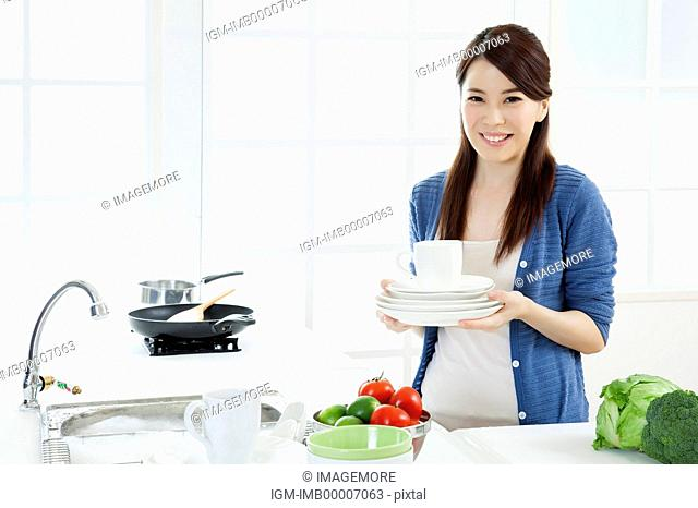 Young woman holding plates and cup with smile