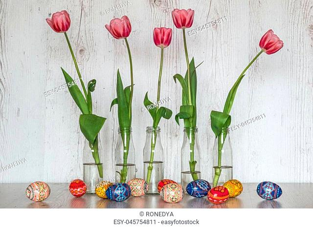 Easter Background with easter eggs and pink tulips in glass bottles on light wooden background