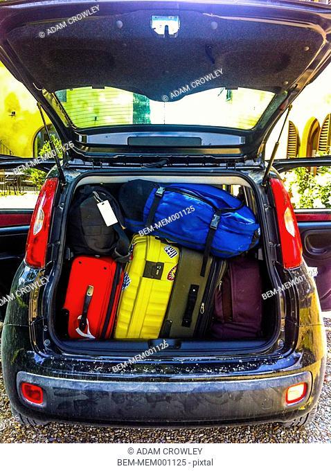 Luggage stuffed in car trunk