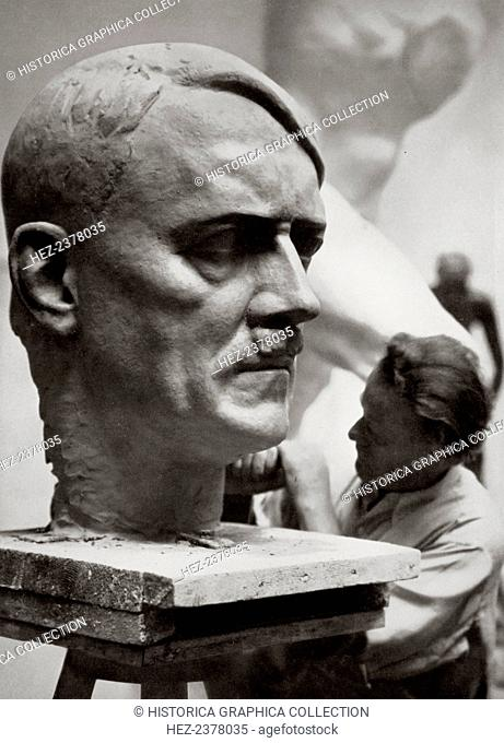 A sculptor working on a large portrait bust of Adolf Hitler, Germany, 1936. Artistic creative work expressive of the new national spirit