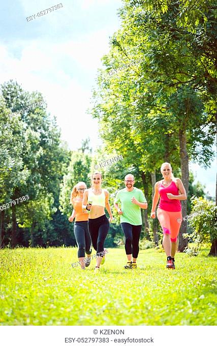Family with personal Fitness Trainer jogging on a meadow