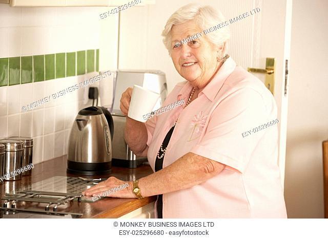 Retired Senior Woman In Kitchen Making Hot Drink