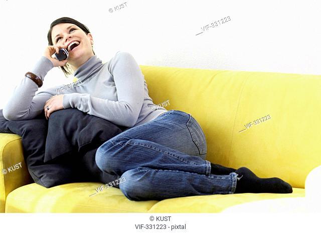Junge Frau liegt auf Sofa und telefoniert - Amstetten, Haka K³chenstudio, Da, Niederoesterreich, Austria, 27/12/2005