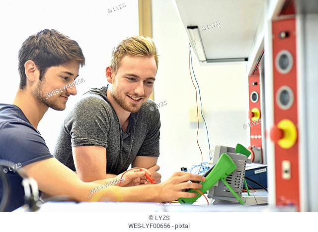 Smiling technical students looking at device