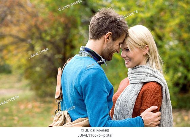 Young couple face to face on college campus
