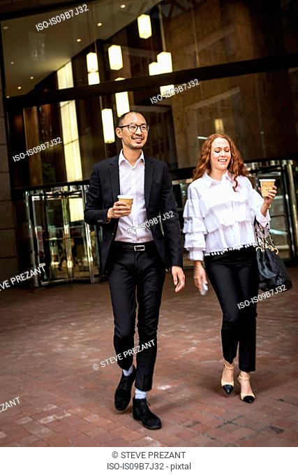 Young businesswoman and man with takeaway coffee strolling on sidewalk, New York, USA