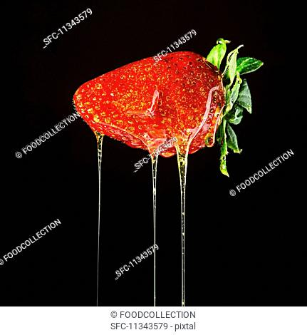A strawberry dripping with honey (close-up)