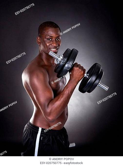 Young African Man Exercising With Dumbbells