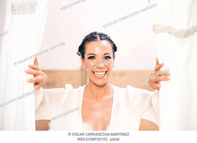Portrait of happy woman opening curtain