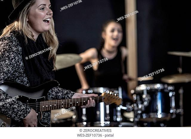 Female rock guitarist and drummer at recording studio