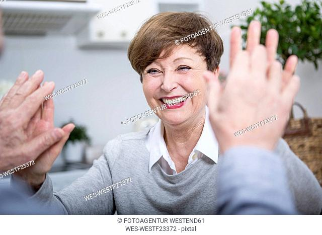 Smiling senior woman giving man high five