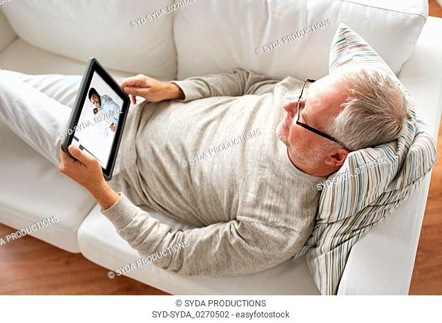 senior man watching webinar on tablet at home