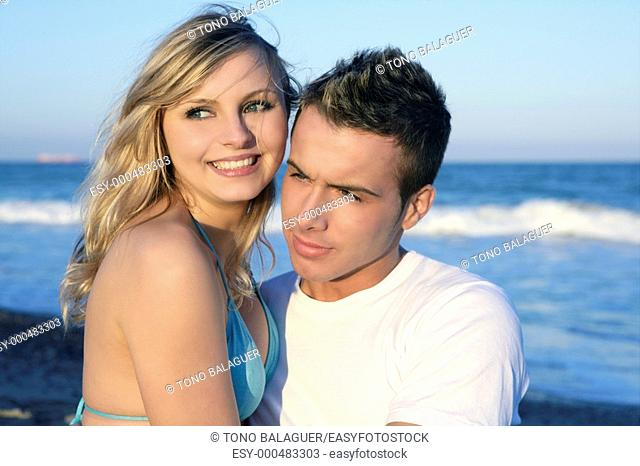 Happy beautiful young couple posing on the blue beach