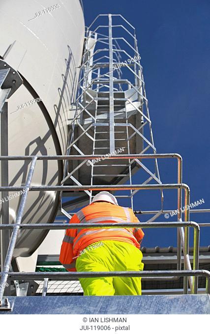 Engineer wearing hi viz climbing steel ladder of cement works tower