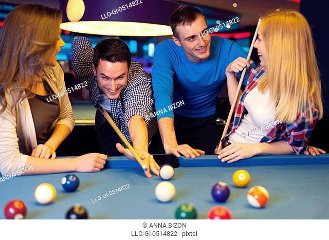 Group of four friends playing billiard. Rzeszow, Poland