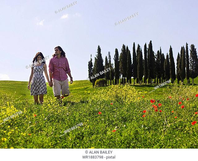 Italy, Tuscany, Val D'Orcia, Young couple walking on meadow