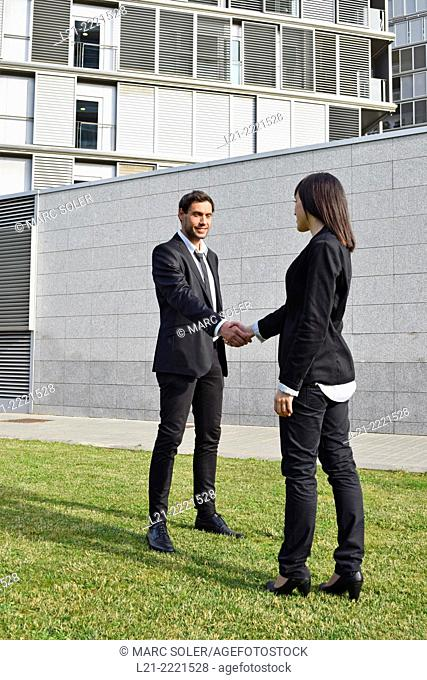 Businessman and woman shaking hands outside