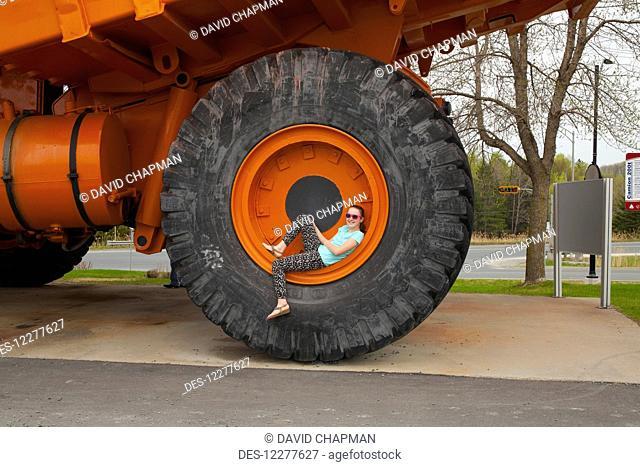 Girl sitting inside wheel rim of 200 ton truck used in Jeffery mine; Asbestos, Quebec, Canada